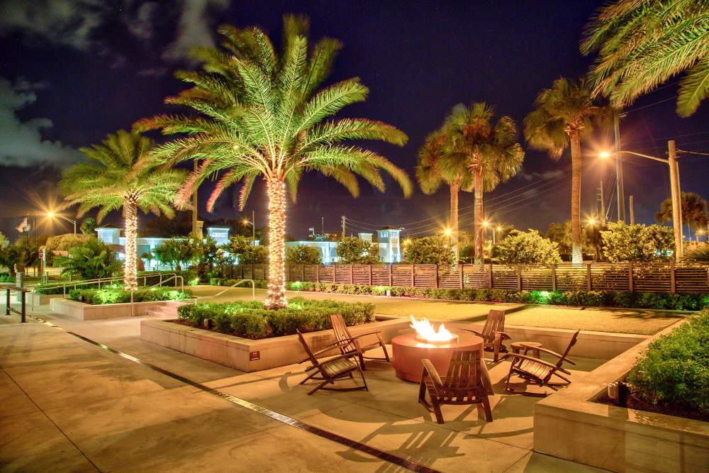 Firepit area and lighted palms at night